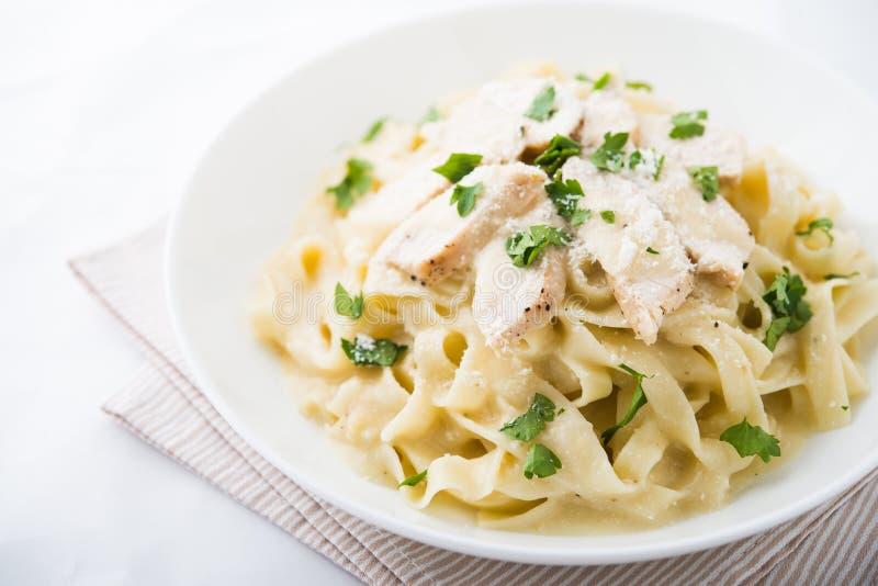 Fettuccine Alfredo de las pastas con el pollo, el parmesano y el perejil en el cierre blanco del fondo para arriba imagenes de archivo