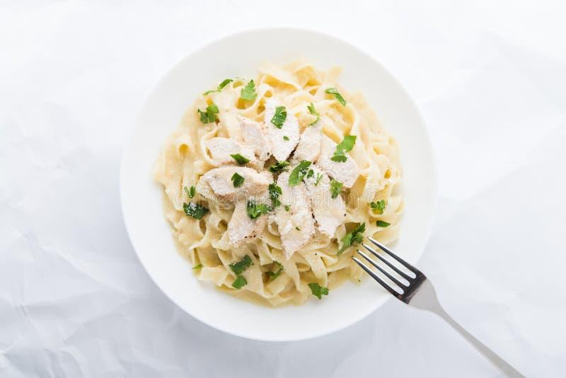 Fettuccine Alfredo de las pastas con el pollo, el parmesano y el perejil en la opinión superior del fondo blanco fotos de archivo libres de regalías