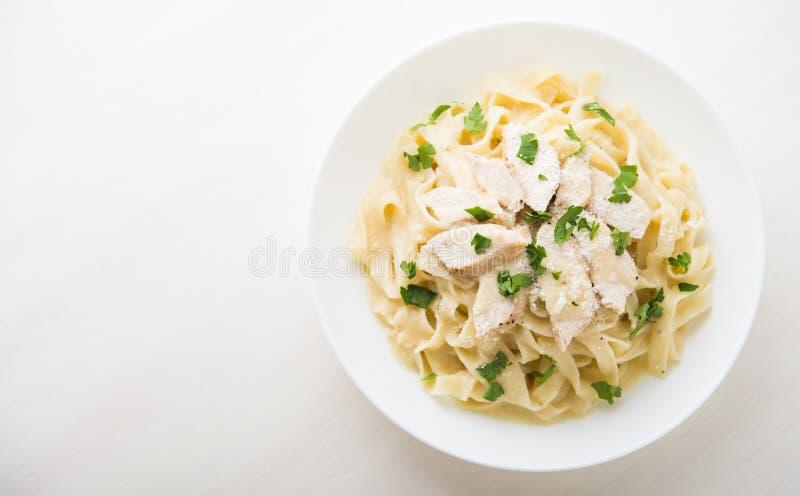 Fettuccine Alfredo de las pastas con el pollo, el parmesano y el perejil en la opinión superior del fondo blanco fotos de archivo