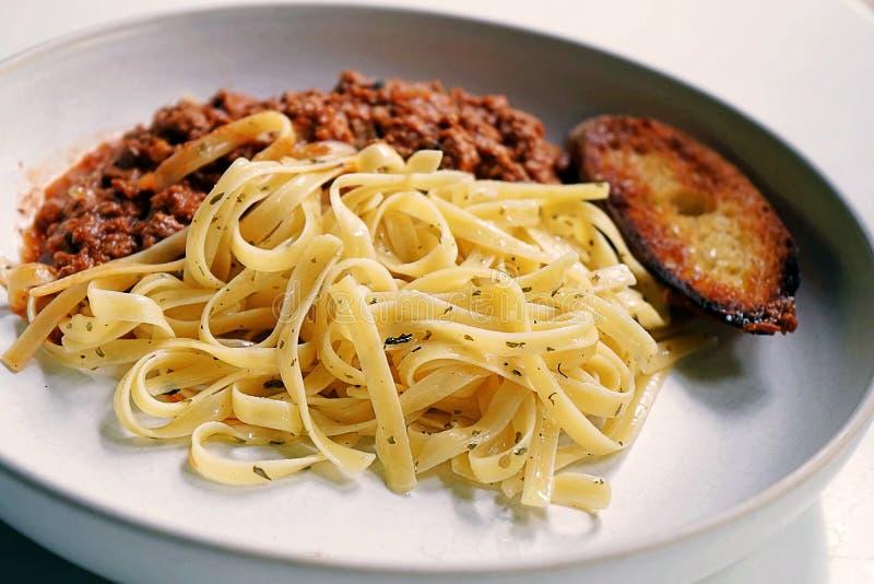 Fettuccine Bolognese diende met een grote die toost met geraspte die kaas wordt bedekt en op witte schotel wordt geplaatst stock fotografie
