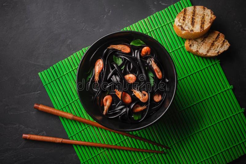 Черные макаронные изделия Fettuccine чернил кальмара с креветками или креветками, петрушкой, chili в вине и соусом масла стоковое фото
