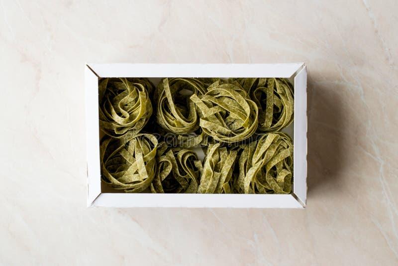 Fettuccine cru italien d'épinards de pâtes dans la boîte/tagliatelles photo libre de droits