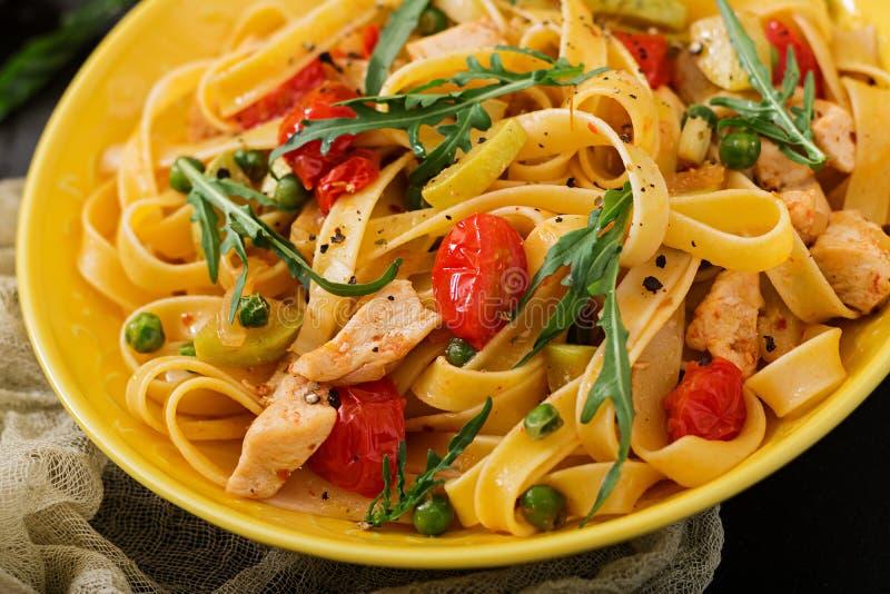 Fettuccine de las pastas con el prendedero del tomate, del calabacín y del pollo imagenes de archivo