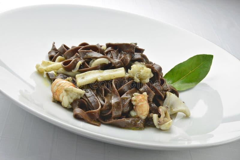 Fettuccine del cioccolato del piatto della pasta con i gamberetti e la seppia 2 immagini stock