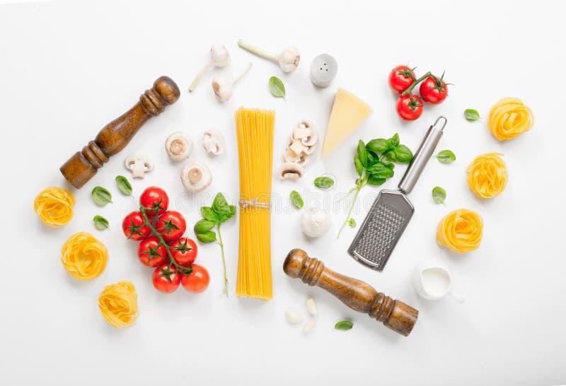 Fettuccine et spaghetti avec des ingrédients pour faire cuire la PA italienne photographie stock libre de droits