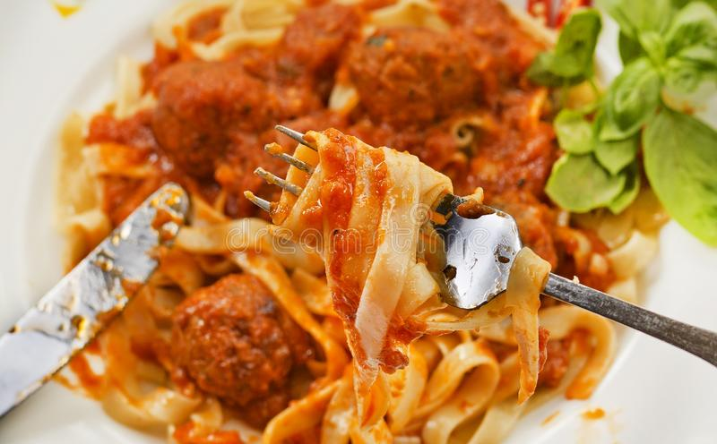 Fettuccine and Meatballs on a fork close-up royalty free stock image