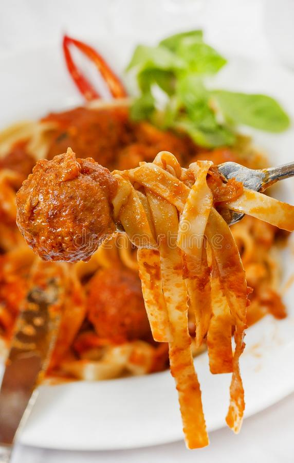 Fettuccine and Meatballs on a fork close-up royalty free stock photography