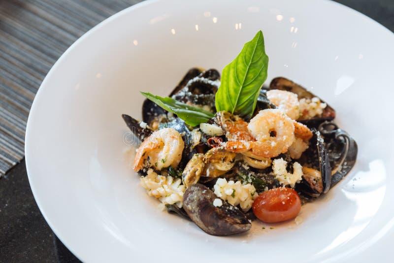 Fettuccine negro con el camarón, el calamar y la almeja Pastas de la tinta del calamar de los mariscos imágenes de archivo libres de regalías