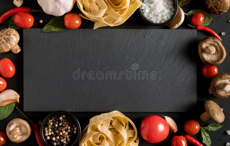Fettuccine tagliatelle paste with herbs and spices with slate bo. Ard copy text space royalty free stock photography