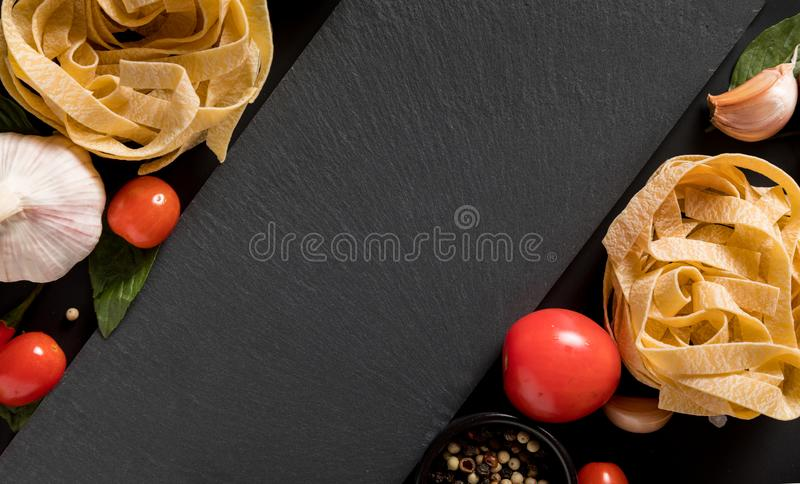 Fettuccine tagliatelle paste and slate board with mushrooms, her royalty free stock images