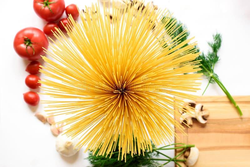 Fettuccine y espaguetis con los ingredientes para cocinar las pastas en un fondo blanco, visión superior imagen de archivo