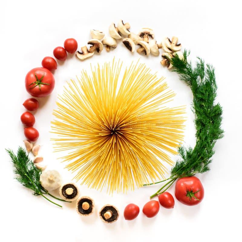 Fettuccine y espaguetis con los ingredientes para cocinar las pastas en un fondo blanco, visión superior fotos de archivo libres de regalías