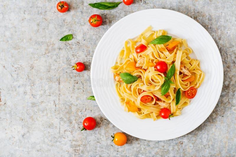 Fettuccinepasta i tomatsås med höna, tomater dekorerade med basilika fotografering för bildbyråer
