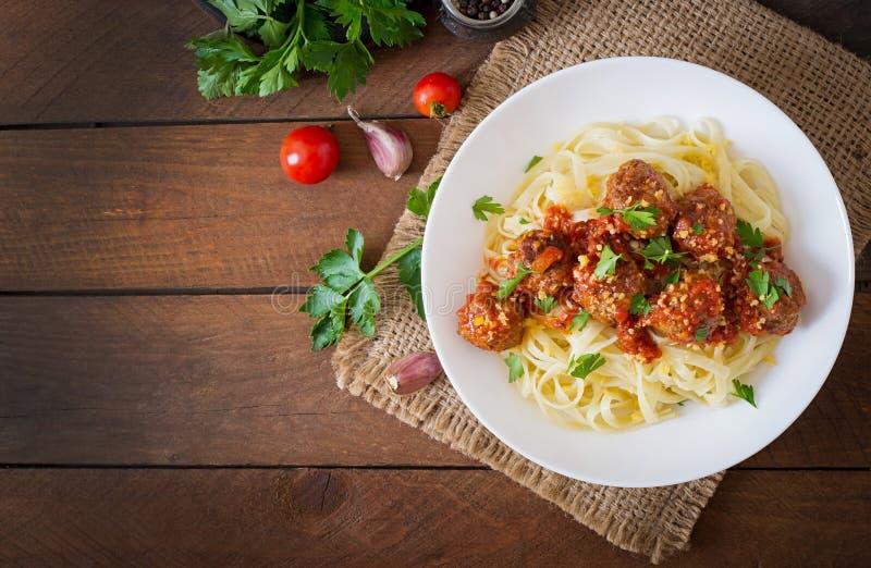 Fettuccinepasta med köttbullar i tomatsås arkivbilder