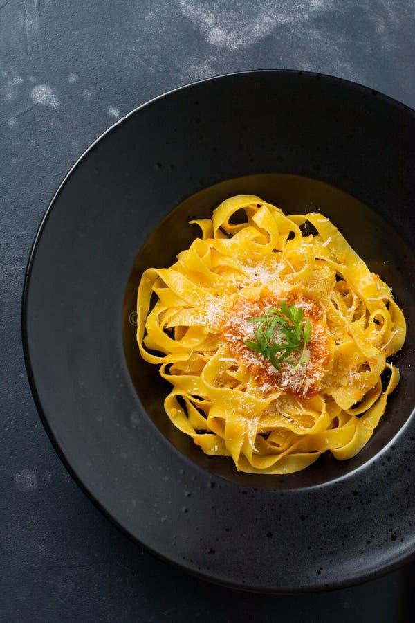 Fettuccinepasta med traditionell italienarePassat sås och parmesanost i svart platta på mörk bakgrund arkivbilder