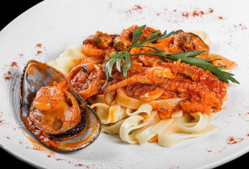 Fettuccineteigwaren mit Meeresfrüchten, Miesmuscheln, Krake, Austern, Tomatensauce und Kräutern lizenzfreie stockbilder