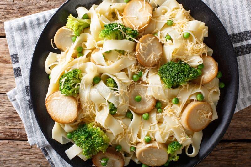 Fettuccineteigwaren mit Pilzkönigauster, Brokkoli und Erbsen c lizenzfreie stockfotos