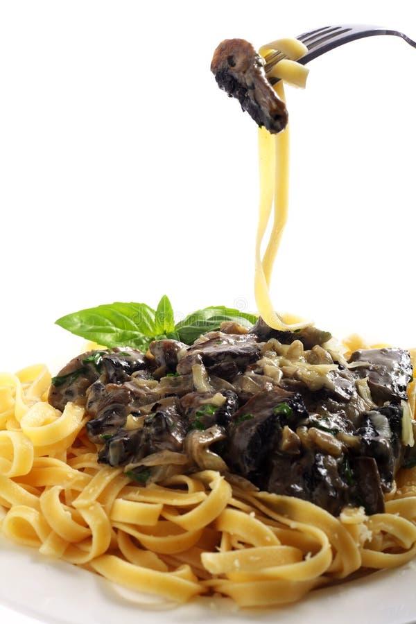 Fettuccini e cogumelo em uma forquilha imagem de stock