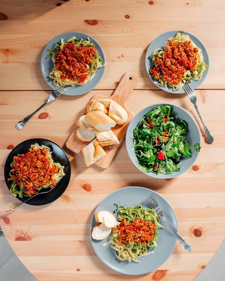 Fetuchini makaron z wołowina pomidorowym kumberlandem na drewno stole, włoski jedzenie Świeża sałatka w szarym talerzu z arugula obraz stock