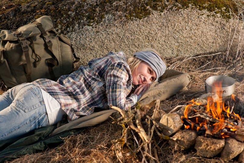 Feu de camp augmentant le sommeil de sac à dos de femme photographie stock
