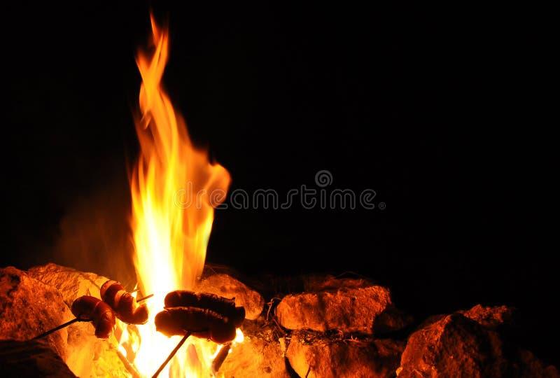 Feu de camp pendant la nuit et les saucisses grillées image libre de droits