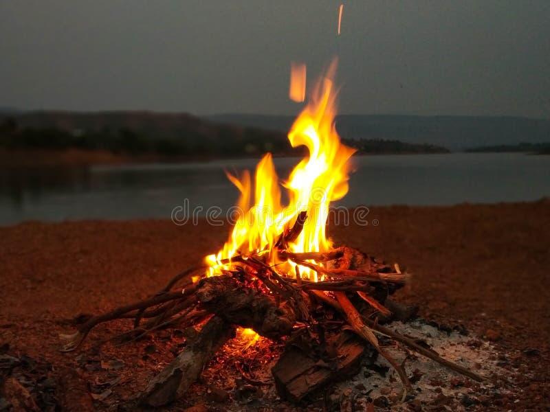feu de camp près de rivière et de montagne photos stock