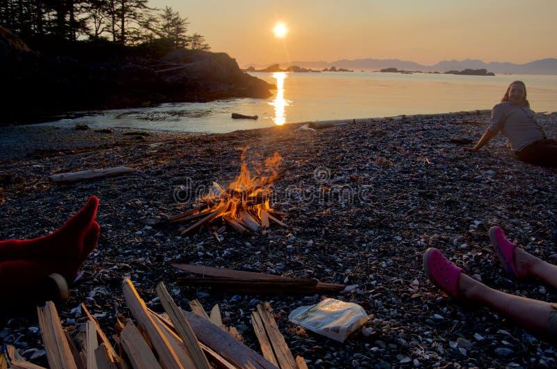 Feu de camp sur la plage au coucher du soleil avec des campeurs détendant tout près image libre de droits