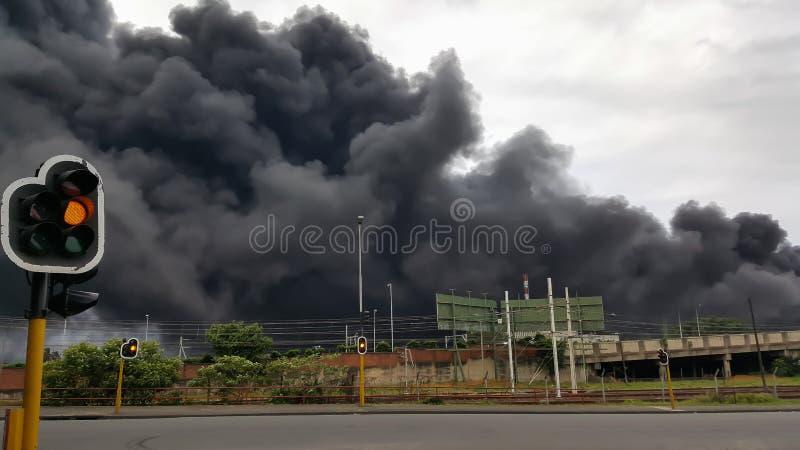 Feu de signalisation dans la ville avec de la fumée toxique noire à l'arrière-plan photos stock
