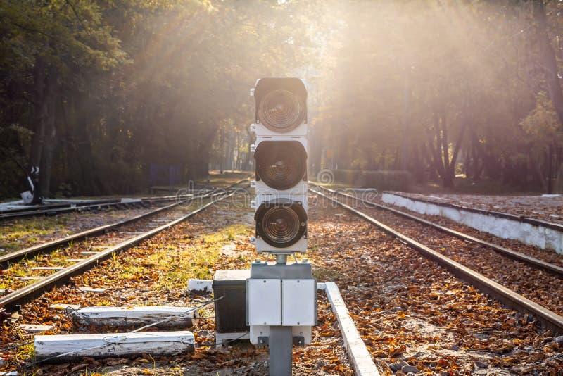 Feu de signalisation ferroviaire avec la fusée naturelle du soleil de baclkight Gare et sémaphore dans la belle forêt d'automne image libre de droits