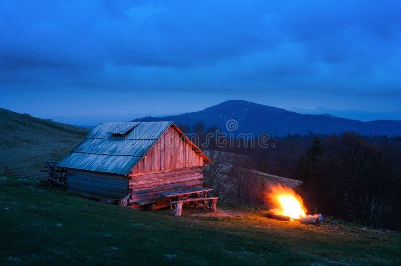 Feu près d'une maison en bois dans les montagnes photographie stock libre de droits