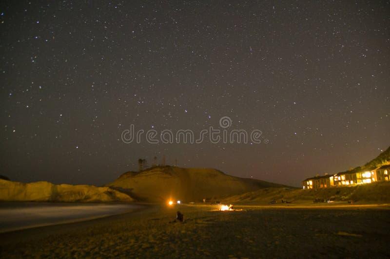 Feuer auf dem Strand mit Sternen und Kap Kiwanda im Hintergrund stockfotografie
