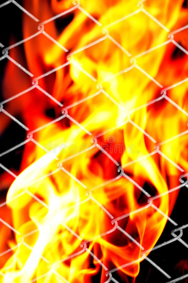 Feuer in einem Metallgitter stockbild