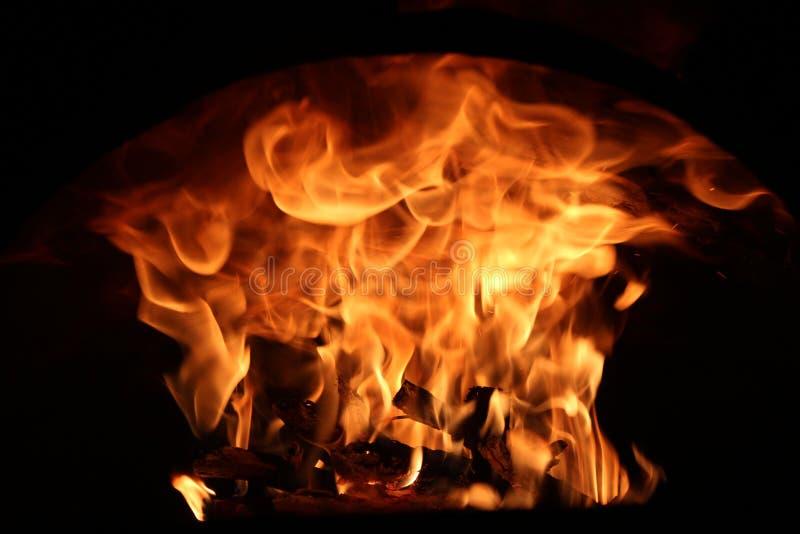 Feuer im Kamin auf einem dunklen Hintergrund stockfotografie