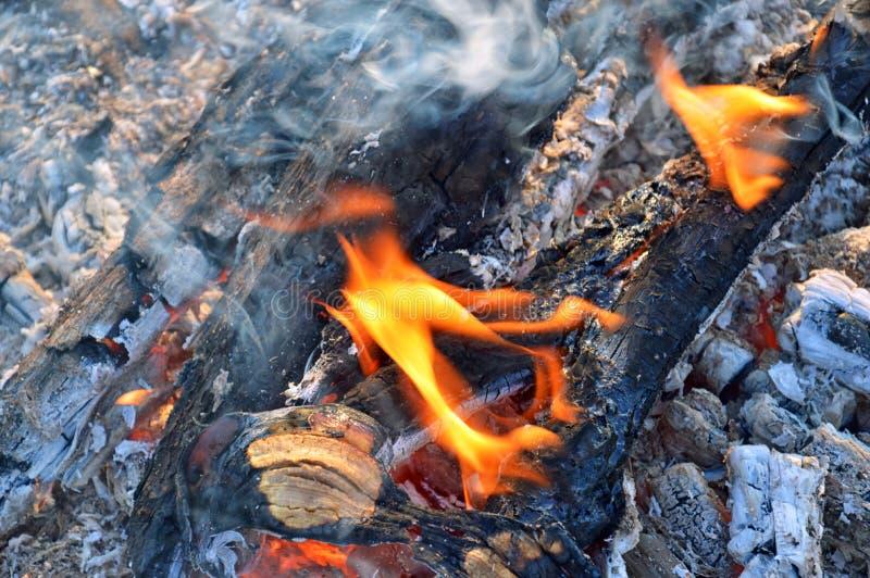 Feuer mit schwarzen Kohlen, orange Flammen, blauem Rauche und grauer Asche stockfotografie