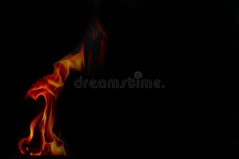Feuerflammen auf schwarzer Hintergrundbeschaffenheit der abstrakten Kunst, brennende glühende Funken steigen vom großen Feuer her stockbild