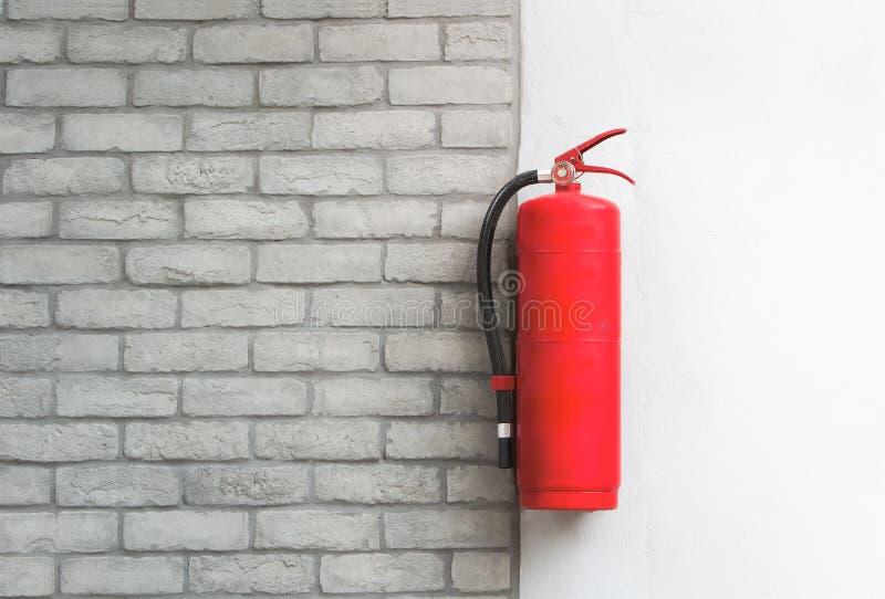 Feuerlöscher auf weißem Backsteinmauerhintergrund stockbild