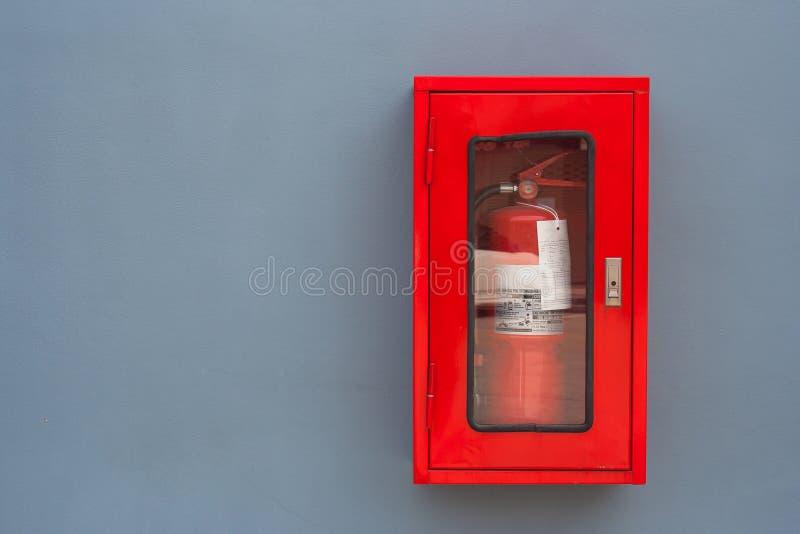 Feuerlöscher im roten Kabinett auf grauer Wand an den externen Gebäuden lizenzfreie stockbilder
