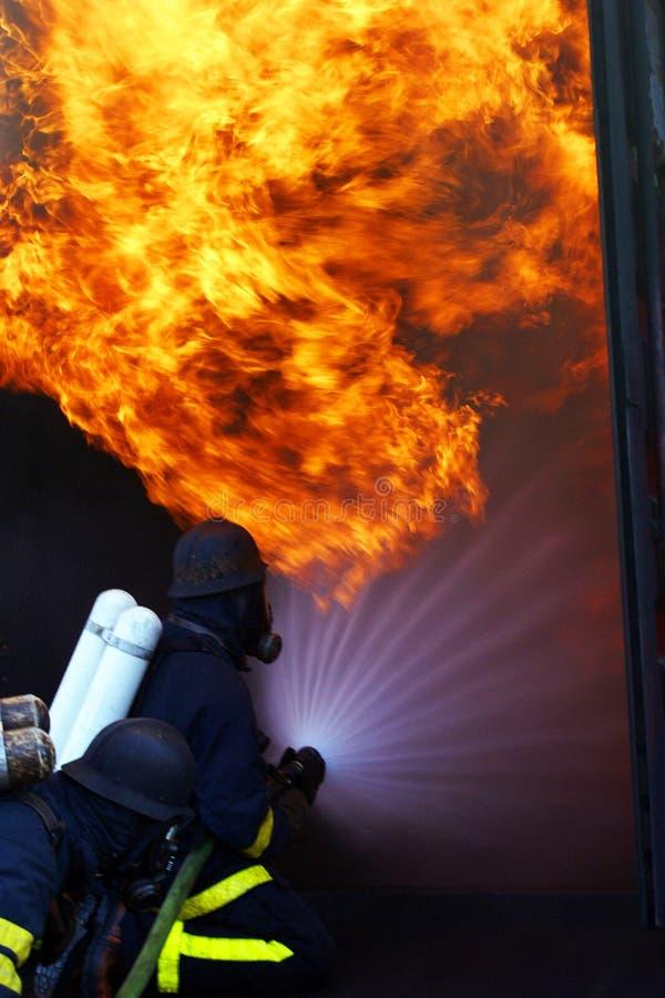 Feuermänner in brennendem Gebäude der Tätigkeit stockbilder