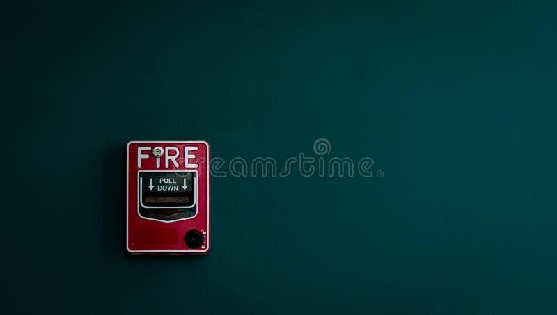 Feuermelder auf dunkelgrüner Betonmauer Warnen und Sicherheitssystem Notausrüstung für Sicherheitsalarm Roter Kasten des Feuermel lizenzfreie stockfotos