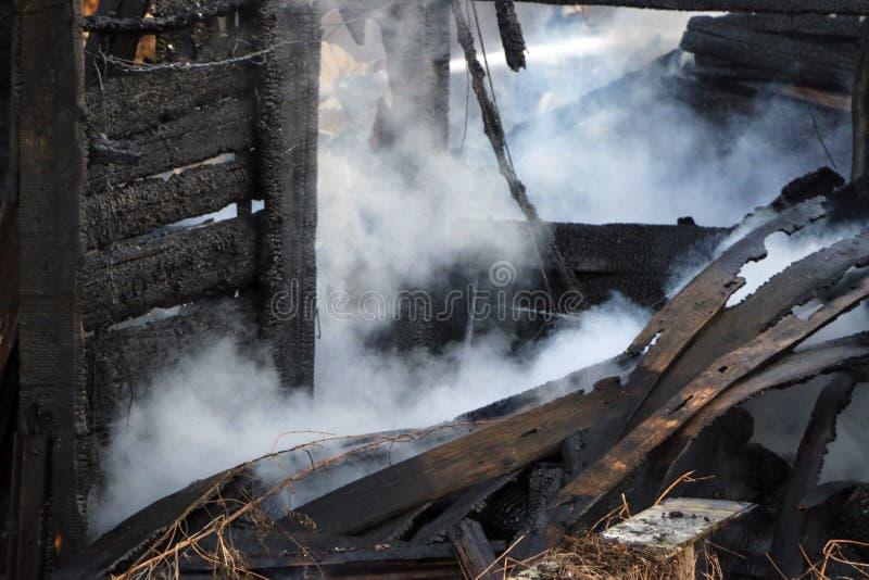 feuersbrunst Ruinen und Überreste eines gebrannten Holzhauses Gebranntes verkohltes Brennholz im dicken Rauche stockfoto