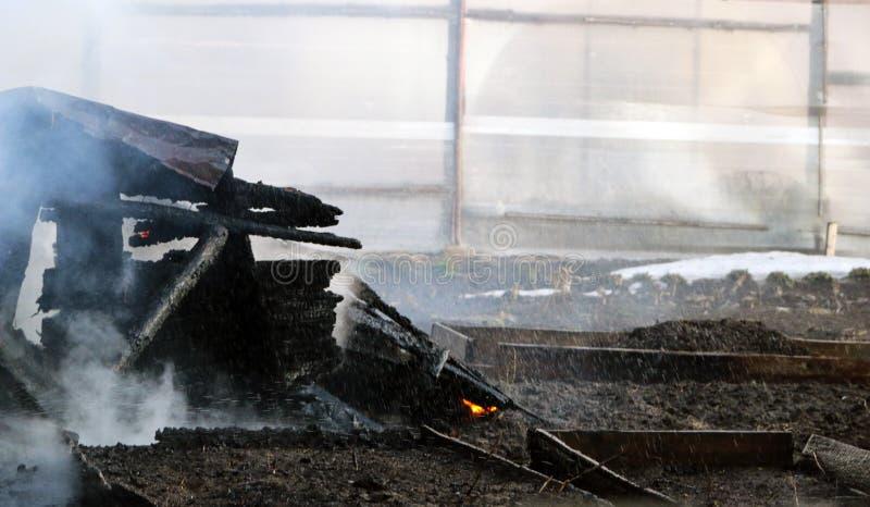 feuersbrunst Ruinen und Überreste eines gebrannten Holzhauses Gebranntes verkohltes Brennholz im dicken Rauche lizenzfreies stockfoto
