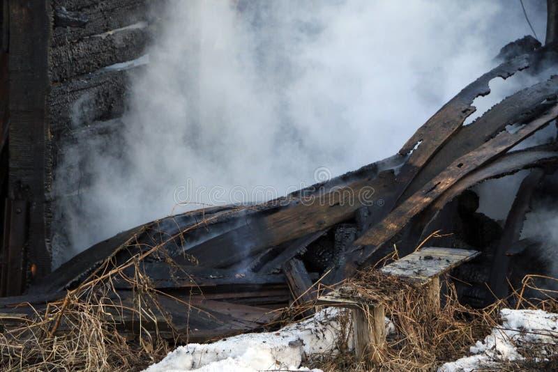 feuersbrunst Ruinen und Überreste eines gebrannten Holzhauses Gebranntes verkohltes Brennholz im dicken Rauche stockbilder