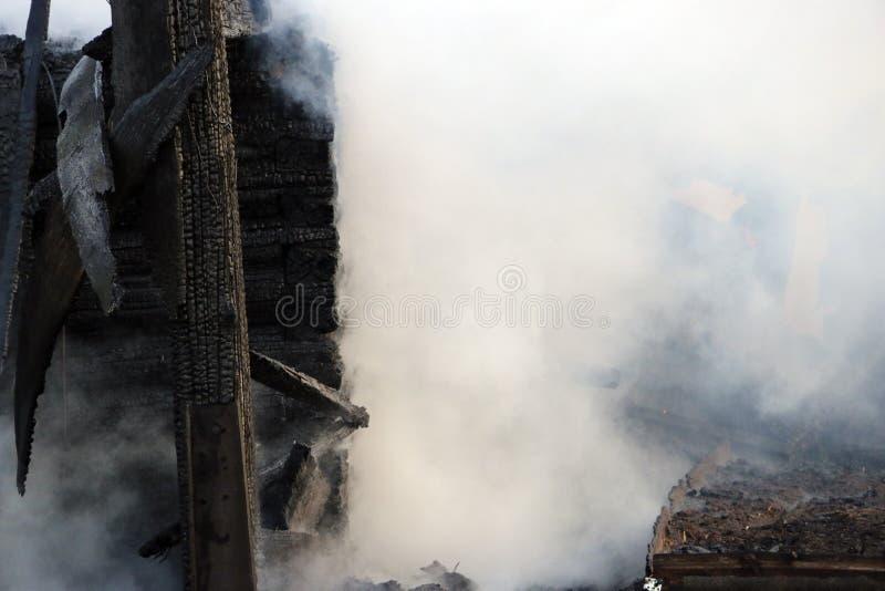 feuersbrunst Ruinen und Überreste eines gebrannten Holzhauses Gebranntes verkohltes Brennholz im dicken Rauche lizenzfreies stockbild