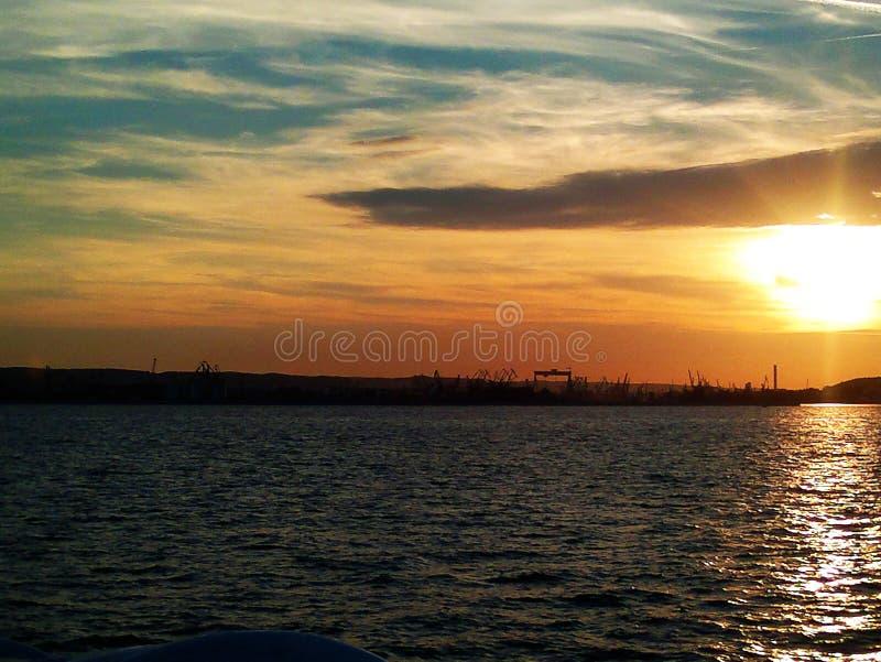 Feuerscheinsonnenuntergang über dem Ostseewasser Verschiedene Farben von Wolken und von Schattenbild der Werft in Gdynia-Stadt, P stockfotografie
