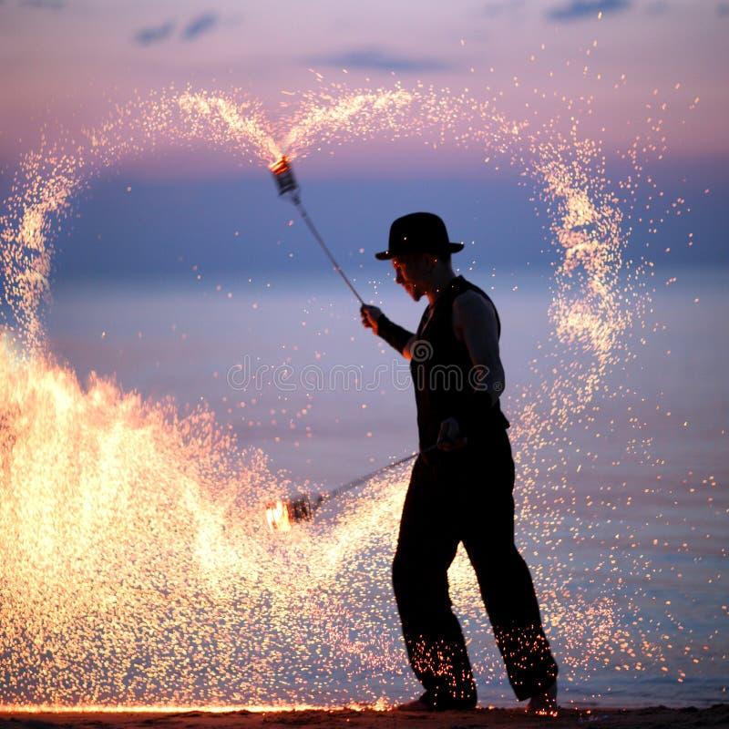 Feuershow auf dem Strand bei Sonnenuntergang lizenzfreie stockfotografie