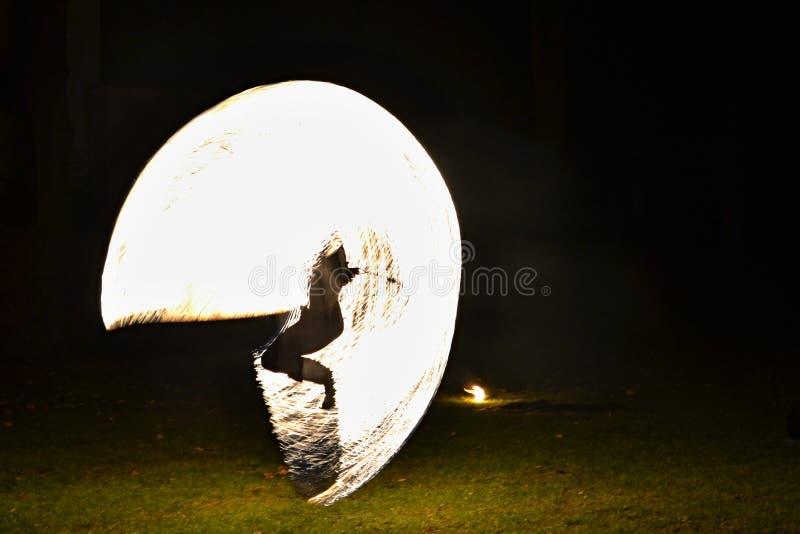 Feuershow - Künstler, die über ein brennendes Springseil in der Dunkelheit springen lizenzfreies stockbild