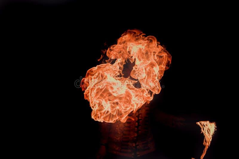 Feuershowkünstler atmen Feuer in der Dunkelheit stockfotografie