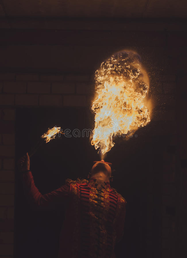 Feuershowkünstler atmen Feuer in der Dunkelheit lizenzfreies stockfoto