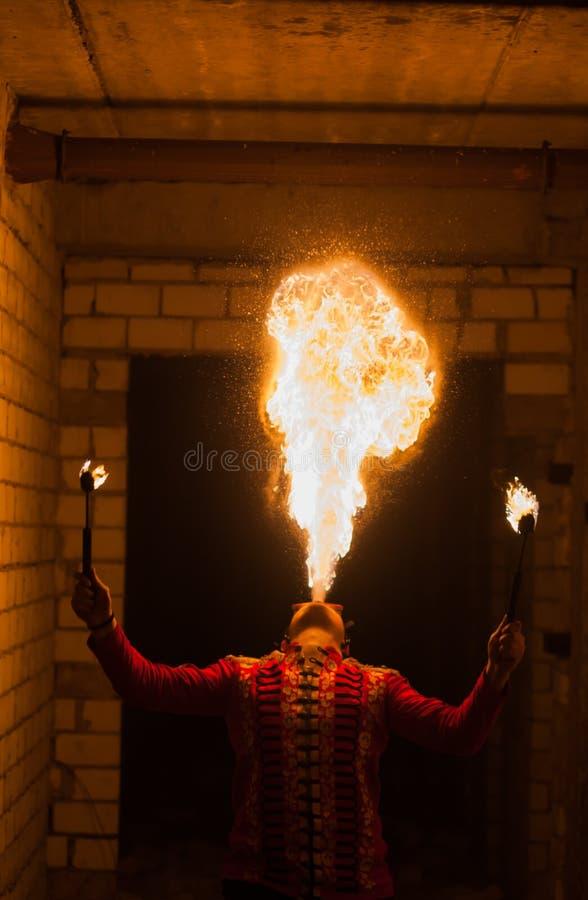 Feuershowkünstler atmen Feuer in der Dunkelheit lizenzfreie stockfotografie