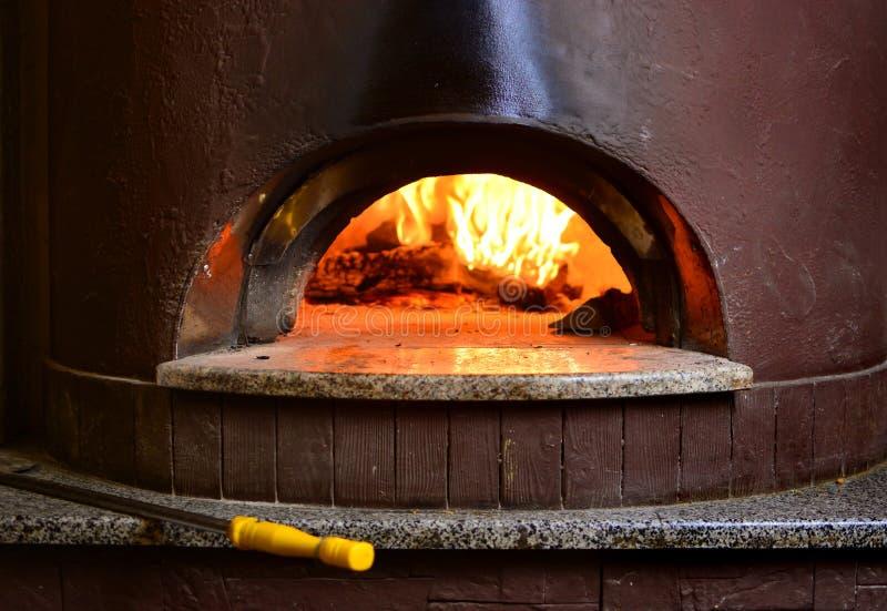 Feuersteinofenofen für die Zubereitung der traditionellen italienischen Pizza Feuerholz, das im Ofen brennt lizenzfreies stockfoto